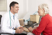 American doctor talking to senior woman in surgery — Stock Photo