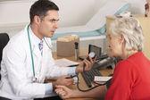 American doctor taking senior woman's blood pressure — Stock Photo