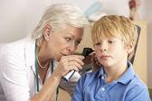 British GP examining young boy's ear — Stock Photo
