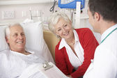 Doctor talking to senior couple on USA Hospital ward — Stock Photo