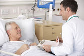 Doctor with senior male patient on USA Hospital ward — Stock Photo