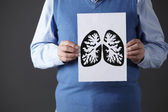 Senior man holding ink drawing of lungs — Stock Photo