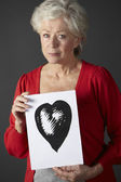 Senior woman holding ink drawing of heart — Stock Photo