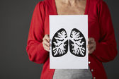 Senior woman holding ink drawing of lungs — Stock Photo