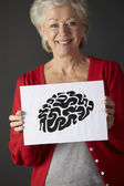 Senior woman holding ink drawing of brain — Stock Photo