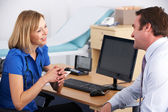 Female UK doctor talking to male patient — Stock Photo