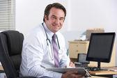 坐在桌前的肖像英国医生 — 图库照片