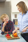 Mother and son preparing food in domestic kitchen — Stock Photo