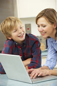 Mother and son using laptop in domestic kitchen — Stock Photo