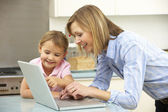 Mother and daughter using laptop in domestic kitchen — Stock Photo