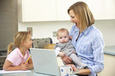 Mother with children using laptop in kitchen — Stock Photo