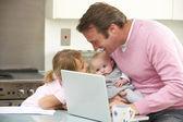 父亲与孩子在厨房中使用笔记本电脑 — 图库照片