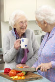 Senior women preparing meal together — Stock Photo