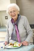 Senior woman enjoying meal in kitchen — Stock Photo