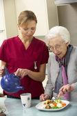 Senior vrouw met verzorger eten van maaltijd thuis — Stockfoto