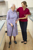 Senior woman and carer in kitchen — Stock Photo