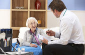 UK GP visiting senior woman at home — Stock Photo