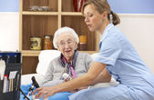 UK nurse visiting senior woman at home — Stock Photo