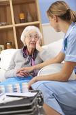 UK nurse visiting senior woman at home — Stock Photo