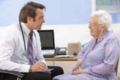 UK GP talking to senior woman patient — Stockfoto