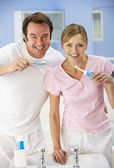 Couple cleaning teeth together in bathroom — Stock Photo