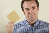 Studio Shot Of Middle Aged Man Holding Wage Packet — Stock Photo