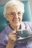 高级女人放松在椅子上,热饮料 — 图库照片