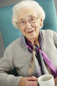 Senior Woman Relaxing In Chair With Hot Drink — Stock Photo