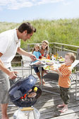 Family on vacation having barbecue — Stock Photo