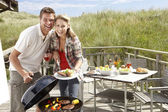 Couple on vacation having barbecue — Stok fotoğraf