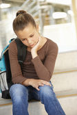Unhappy Pre teen girl in school — Stok fotoğraf