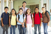 Pre teen schoolchildren with teacher — Stock Photo