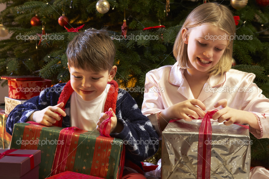 Children Opening Christmas Present In Front Of Tree  Stock Photo #11880827