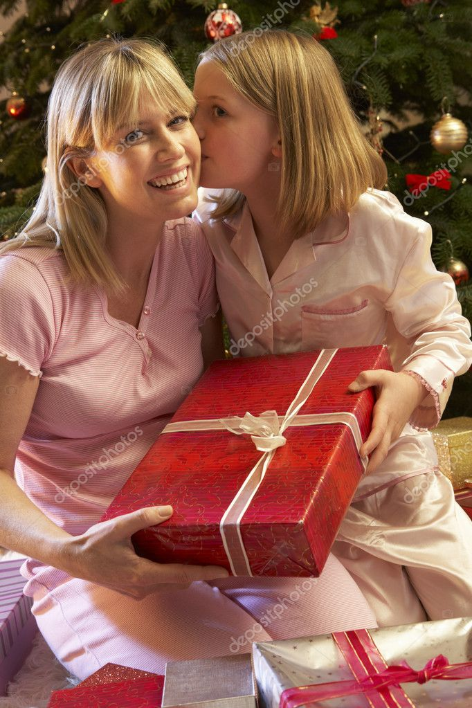 Daughter Giving Mother Christmas Present In Front Of Tree — Stock fotografie #11880847
