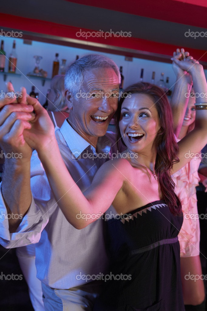 Senior Man Dancing With Younger Woman In Busy Bar — Stock Photo #11880935