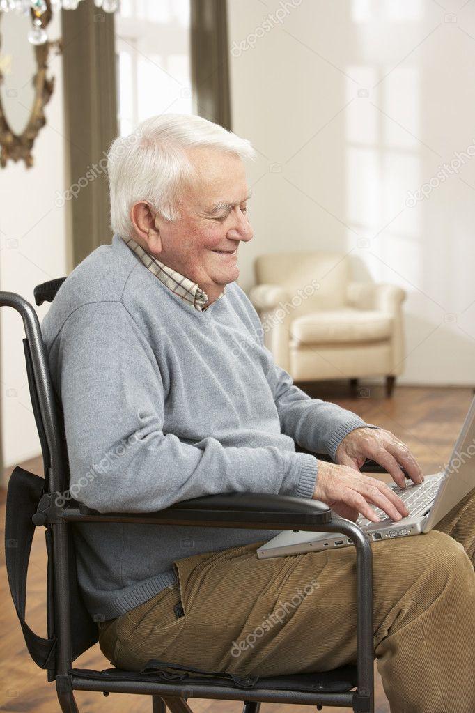 homme senior handicap assis dans le fauteuil roulant l 39 aide d 39 ordinateur portable. Black Bedroom Furniture Sets. Home Design Ideas