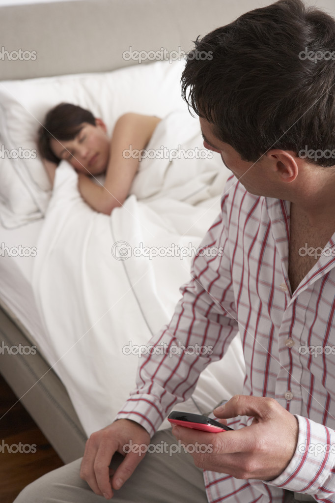 Suspicious Husband Checking Wife's Mobile Phone Whilst She Sleeps — Stock Photo #11881560
