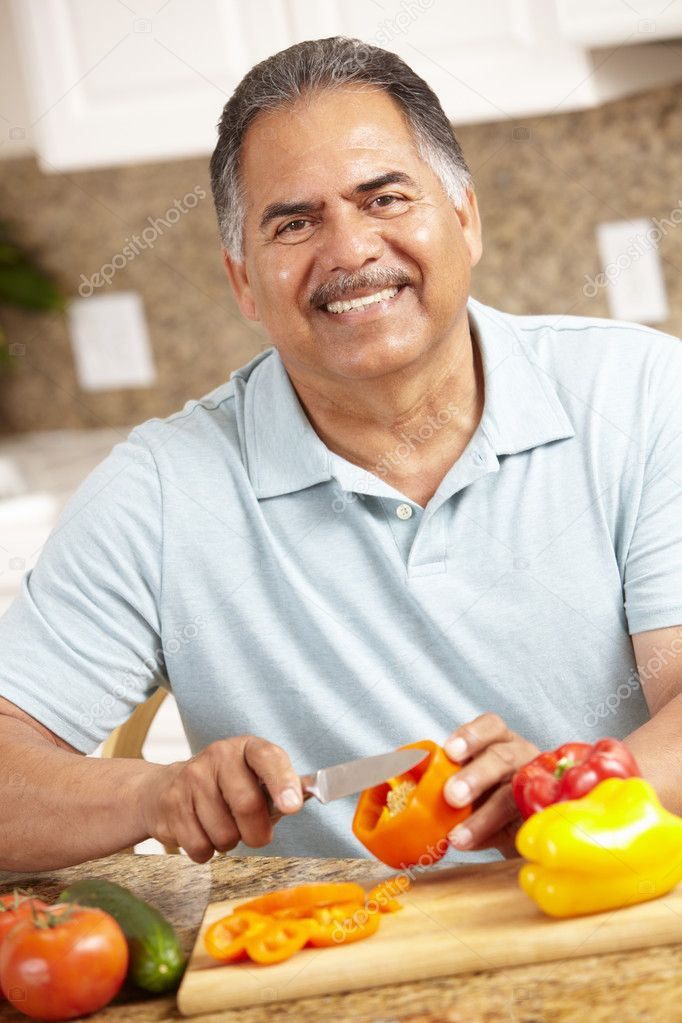 Senior man chopping vegetables  Stock Photo #11884631