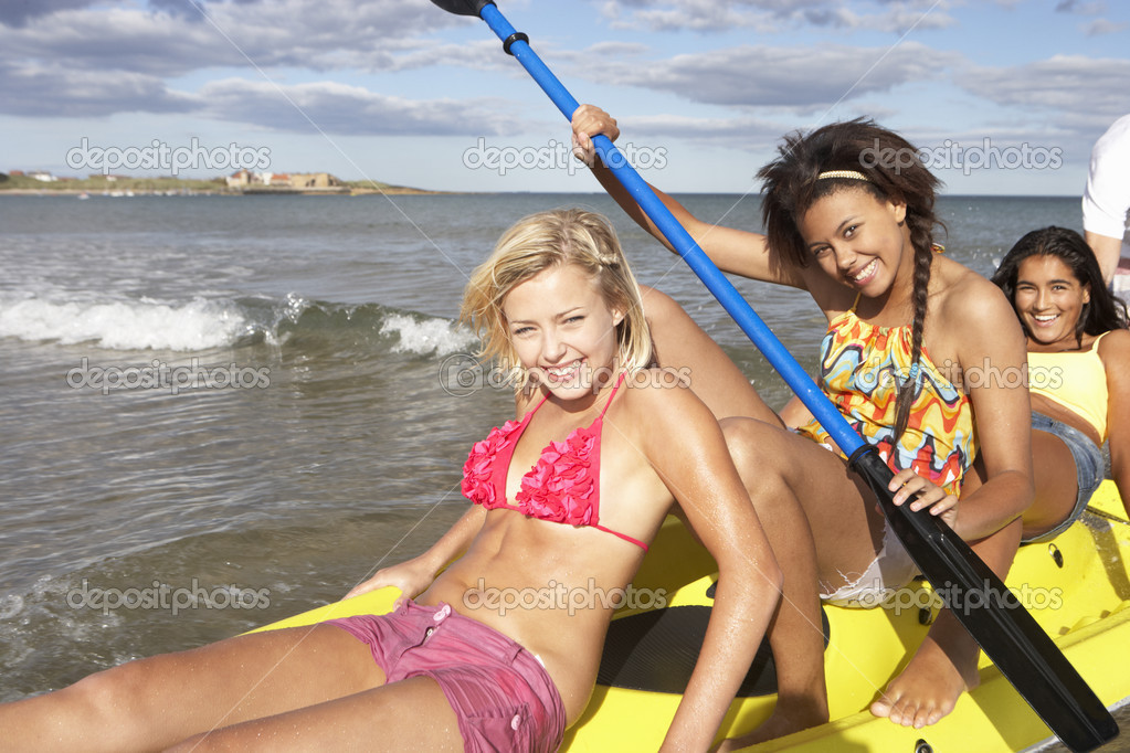 Teenage girls in sea with canoe — Stock Photo #11884874