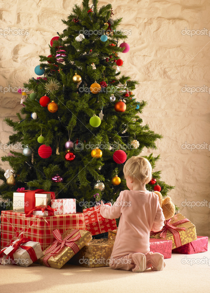 Little girl with parcels round Christmas tree — Zdjęcie stockowe #11884960
