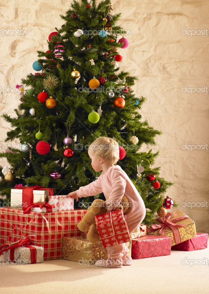 Little girl with parcels round Christmas tree — Stok fotoğraf #11884963