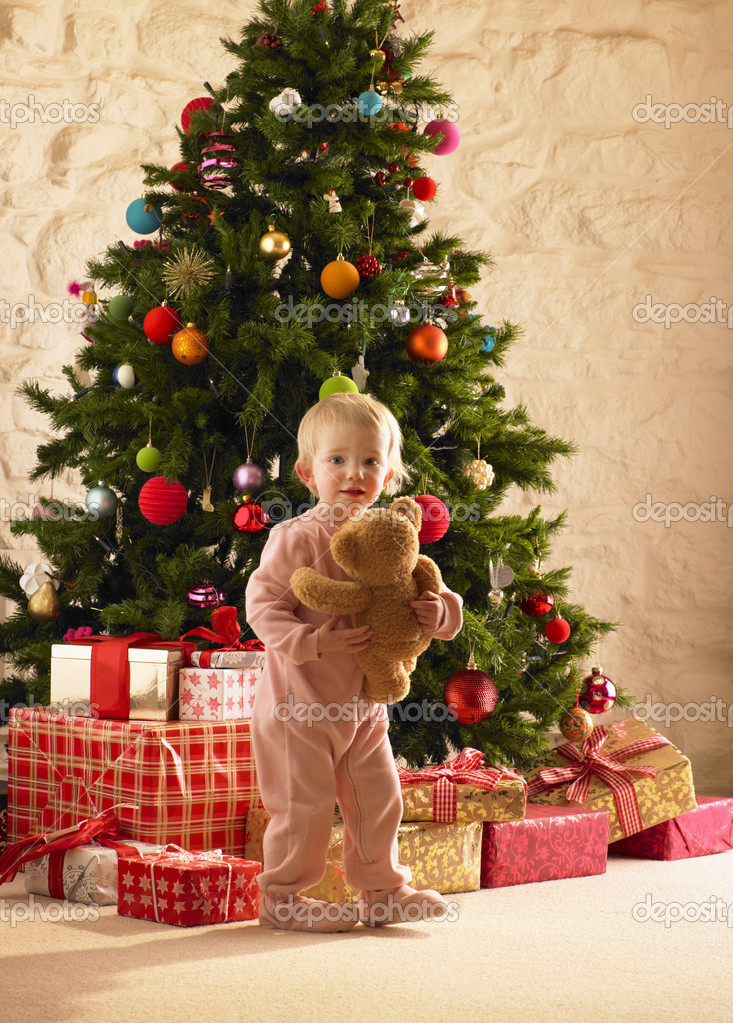 Little girl with parcels round Christmas tree — Stok fotoğraf #11884964