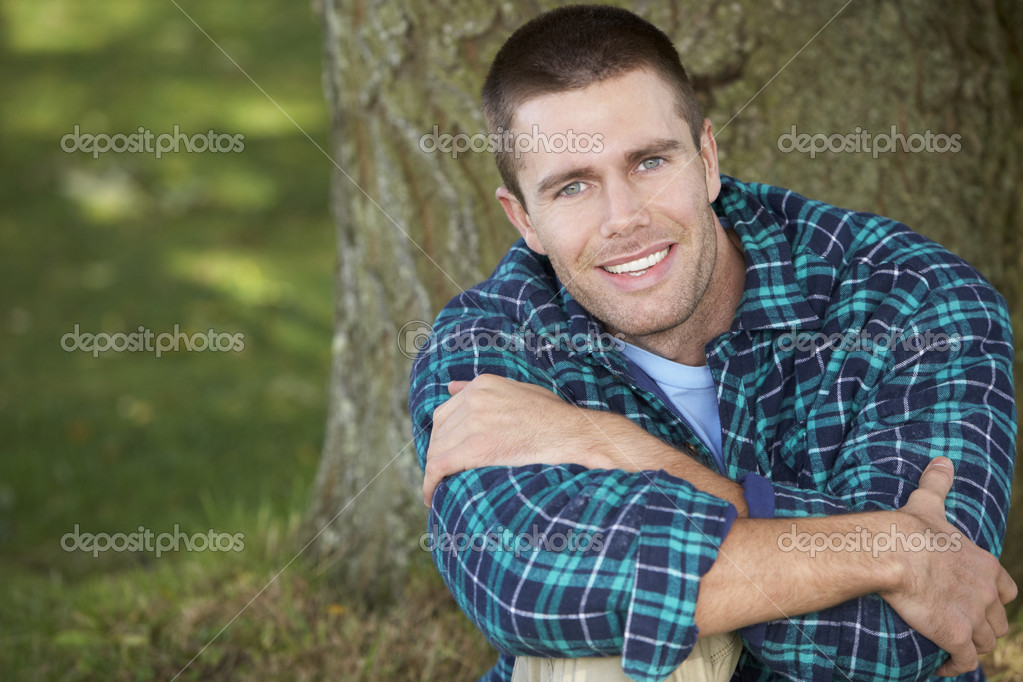 Man sitting against tree trunk — Stock Photo #11885090
