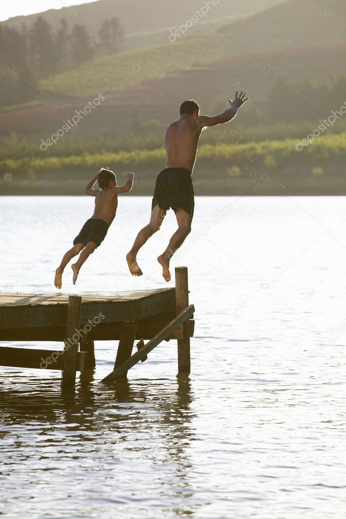 Young man with child jumping to water — Stock Photo #11885874