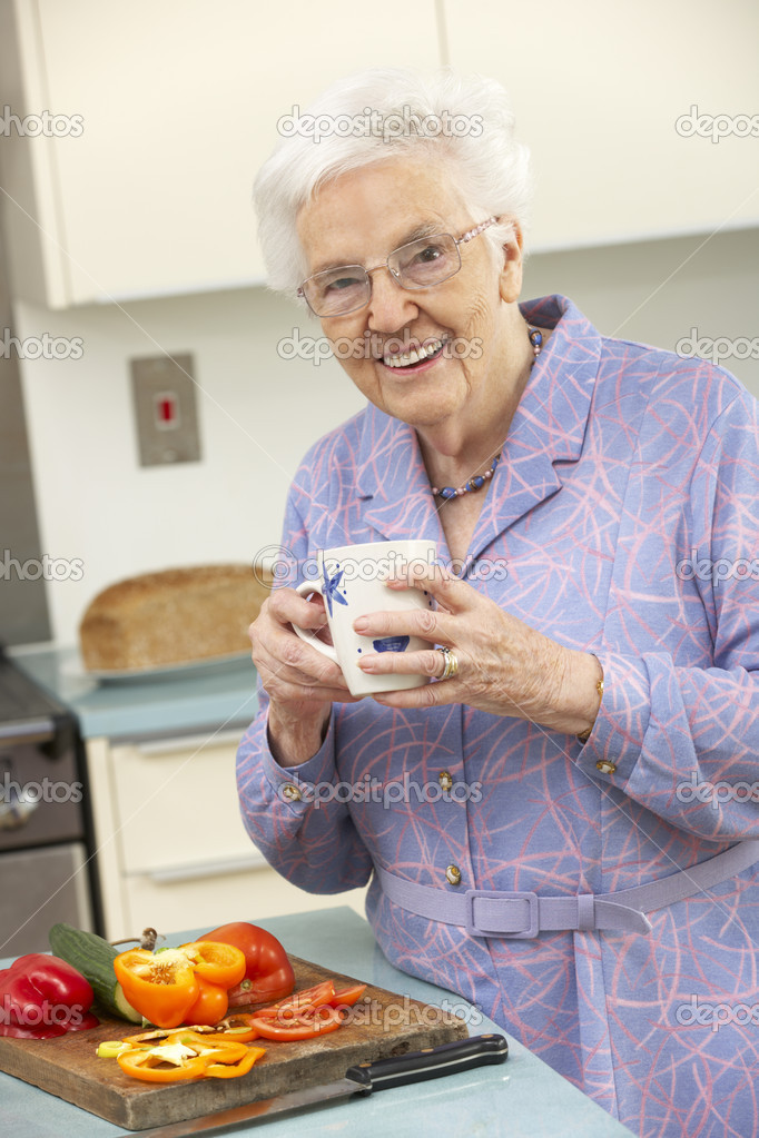 Senior woman preparing food in domestic kitchen — Stock Photo #11888784
