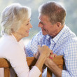 Senior couple sitting outdoors - Stockfoto