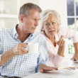 Retired couple arguing at breakfast - Stock Photo