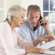 Retired couple with household bills - Stock Photo
