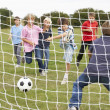 Boys playing soccer in park - Stock Photo