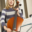 Girl playing cello at home - Stock Photo